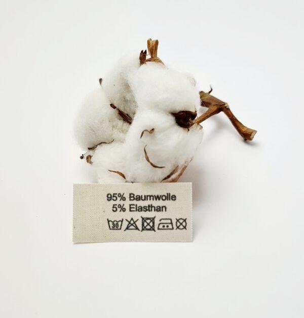 Label aus Naturbaumwollband mit der Aufschrift 95% Baumwolle 5% Elasthan mit Pflegesymbole.